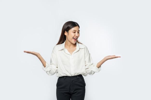 Een jonge vrouw in een wit overhemd en beide handen spreidend