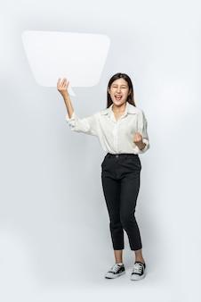 Een jonge vrouw in een wit overhemd met een gedachtendoossymbool