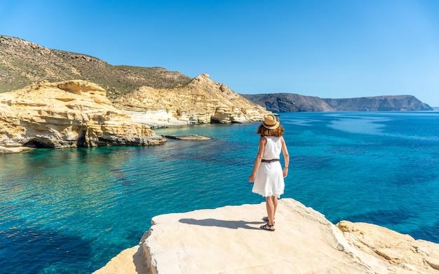 Een jonge vrouw in een witte jurk die op een mooie zomerdag naar de zee kijkt in rodalquilar in cabo de gata, almería