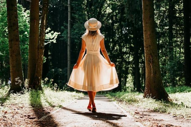 Een jonge vrouw in een witte jurk en een strohoed loopt door het bos. sprookjesbos. achteraanzicht