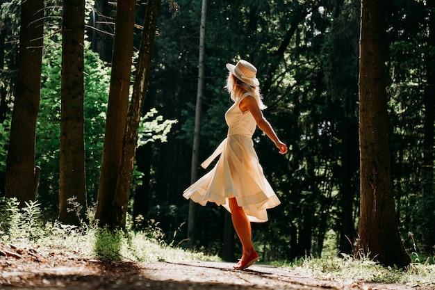 Een jonge vrouw in een witte jurk en een strohoed loopt door het bos