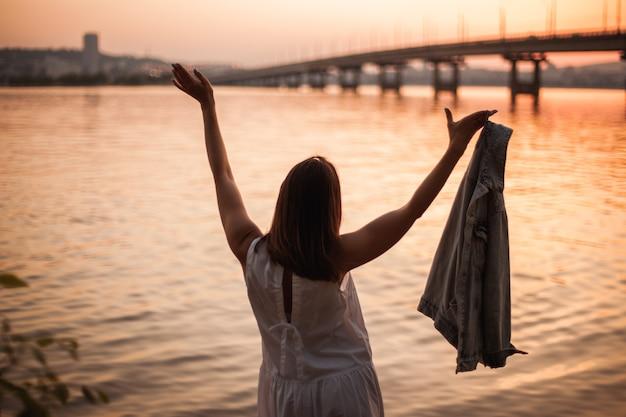 Een jonge vrouw in een witte jurk met opgeheven handen danst op een oranje zonsondergang in de stad en...