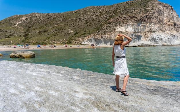 Een jonge vrouw in een witte jurk op het strand van enmedio in cabo de gata op een mooie zomerdag, almería