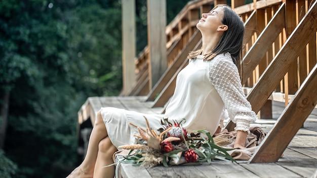 Een jonge vrouw in een witte jurk zit op een houten brug met een boeket exotische bloemen.