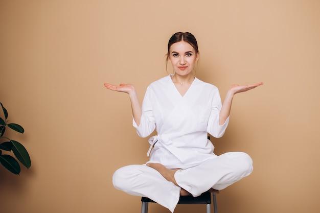 Een jonge vrouw in een witte kimono zit op een stoel en mediteert thuis in een yogahouding