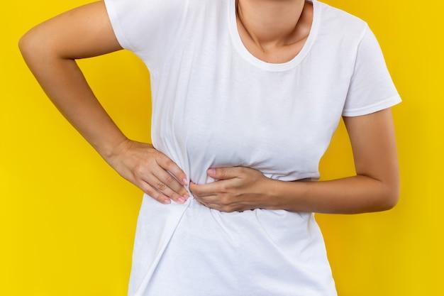 Een jonge vrouw in een witte t-shirt die haar zijde vasthoudt met haar handen geïsoleerd op een gele achtergrond in kleur