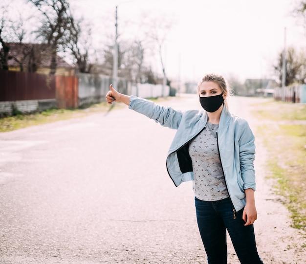 Een jonge vrouw in een zwart medisch masker staat op de weg met een opgeheven hand