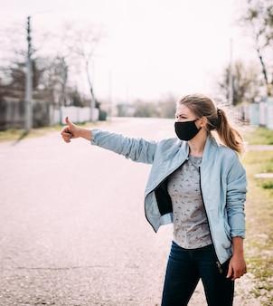 Een jonge vrouw in een zwart medisch masker staat op straat in het dorp