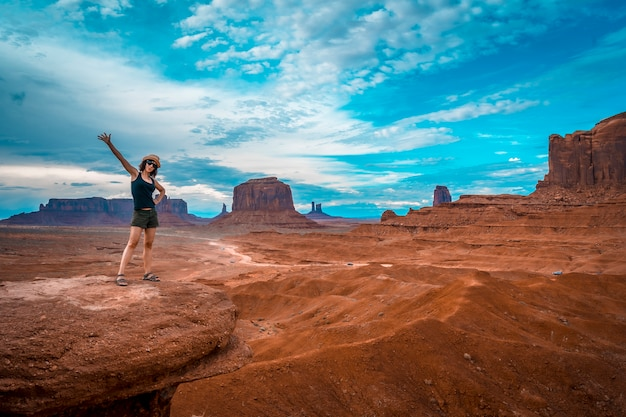 Een jonge vrouw in een zwart t-shirt op john ford's point kijkt naar monument valley.