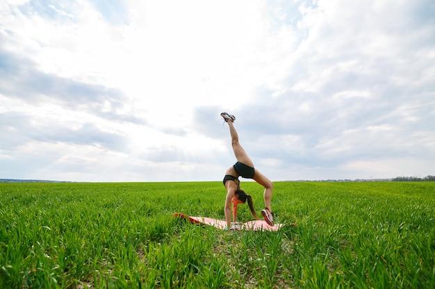 Een jonge vrouw in een zwarte top en korte broek voert een handstand uit. een model staat op haar handen en doet gymnastische splitsingen tegen de blauwe lucht. gezond levensstijlconcept
