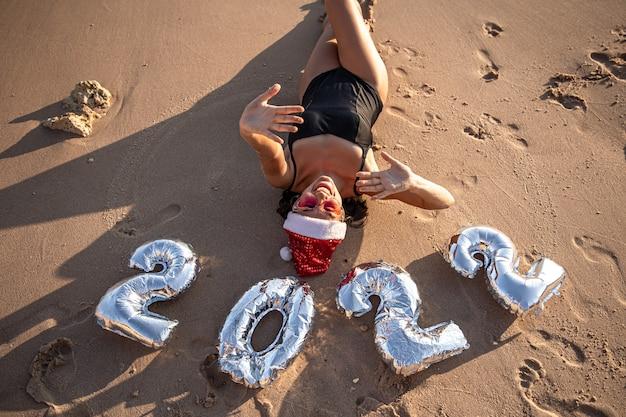 Een jonge vrouw in een zwempak en een kerstman kerstballen in de vorm van de nummers 2022
