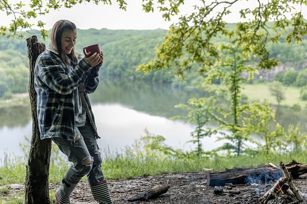 Een jonge vrouw in het bos bij de rivier warmt zich op bij het vuur en drinkt een warm drankje