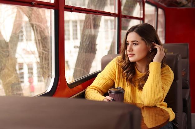 Een jonge vrouw in het openbaar vervoer met een glas koffie