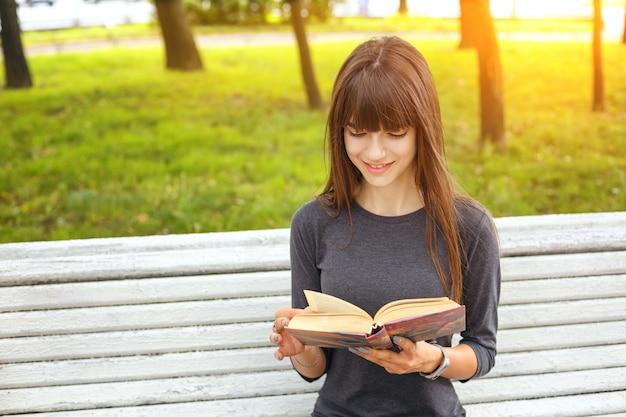 Een jonge vrouw in het park die een boek op een zonnige de zomerdag leest