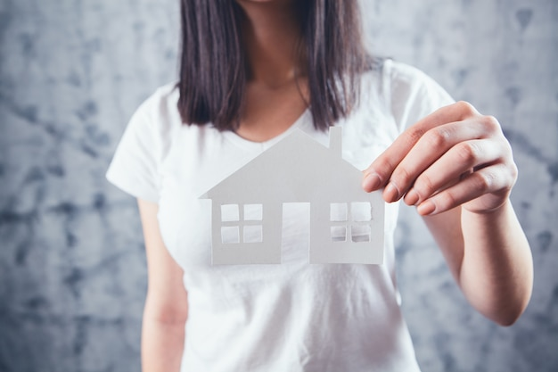 Een jonge vrouw in het wit heeft een huis