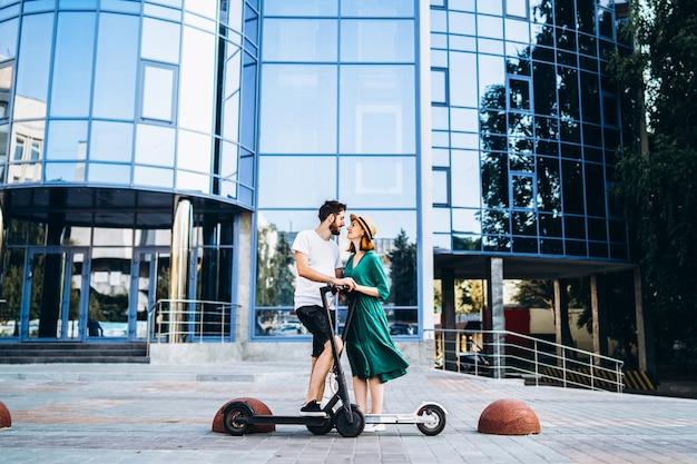 Een jonge vrouw in hoed en man met elkaar praten en genieten van een wandeling op elektrische scooters.