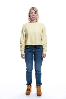 Een jonge vrouw in jeans en een gele trui staat. vrij blond. geïsoleerd op een witte achtergrond. verticaal.