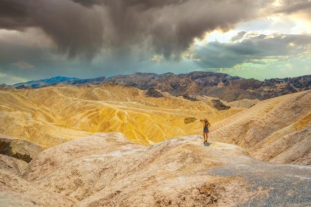Een jonge vrouw in jurk die geniet van het uitzicht op zabriskie point, californië