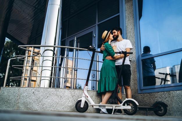 Een jonge vrouw in kleding en een man die met elkaar praten en genieten van een handige manier om door de stad te reizen op elektrische scooters