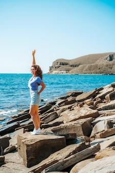Een jonge vrouw in korte broek op een rotsachtig strand gemaakt van natuursteen op de krim