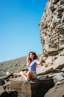 Een jonge vrouw in korte broek zit in een yogahouding op een rotsachtig strand gemaakt van natuursteen op de krim