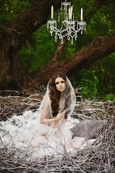 Een jonge vrouw in modieuze kanten lingerie en de sluier zit in het enorme nest en poseert in het groene mystieke bos