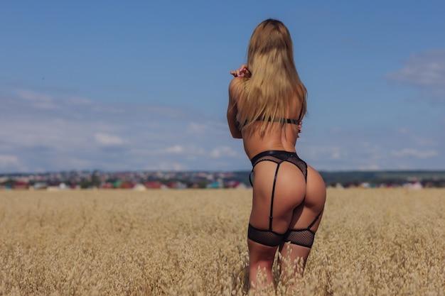 Een jonge vrouw in ondergoed in een tarweveld.
