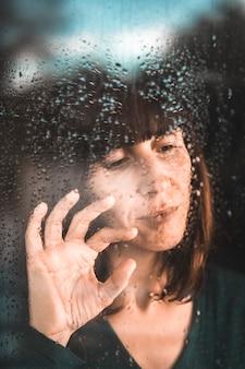 Een jonge vrouw in quarantaine van de covid-19-pandemie in het raam