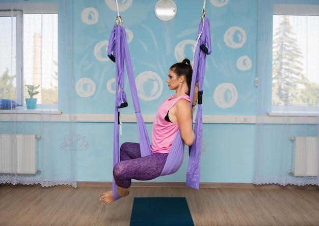 Een jonge vrouw in sportkleding zit in een hangmat en doet oefeningen