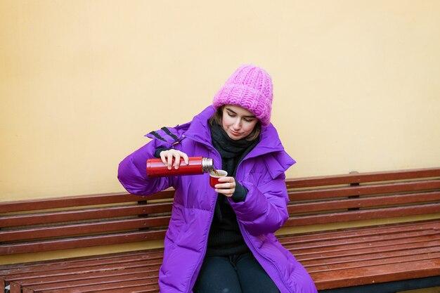 Een jonge vrouw in warme bovenkleding schenkt hete thee uit een thermoskan terwijl ze op een bankje bij de muur zit...