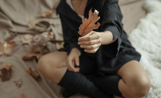 Een jonge vrouw in warme kousen houdt thuis een herfstblad in haar handen.