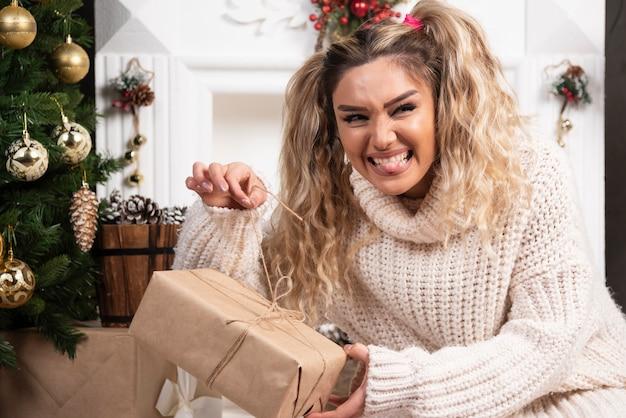 Een jonge vrouw in witte trui met twee dozen met kerstcadeautjes.