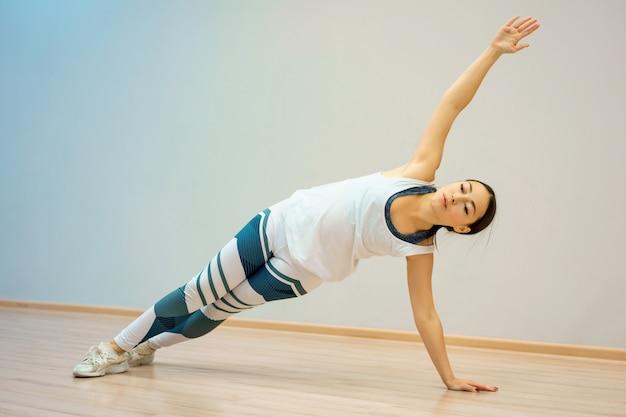 Een jonge vrouw is thuis bezig met fitness op de mat