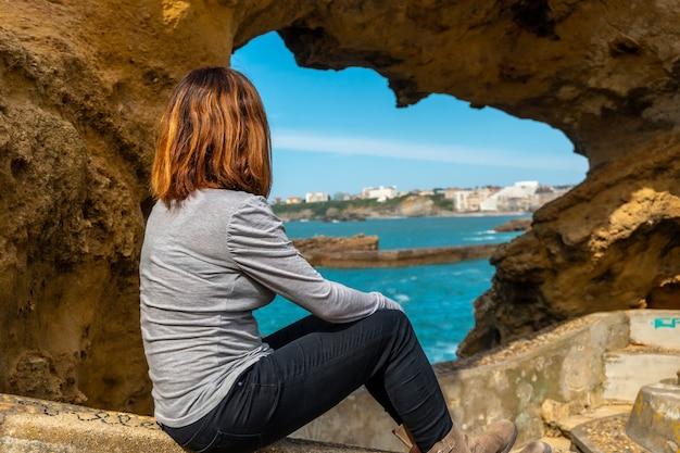Een jonge vrouw kijkt in een raam op de rotsen naast plage du port vieux in biarritz, op vakantie in het zuidoosten van frankrijk
