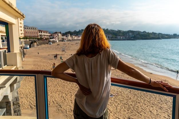 Een jonge vrouw kijkt naar de prachtige grande plage in saint jean de luz bij zonsondergang, vakantie in het zuiden van frankrijk, frans baskenland