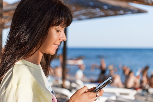 Een jonge vrouw kijkt naar de smartphone.