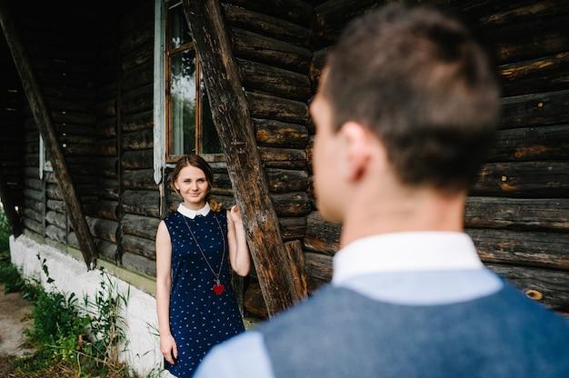 Een jonge vrouw kijkt naar de status van haar man in de buurt van een oud, stijlvol houten huis