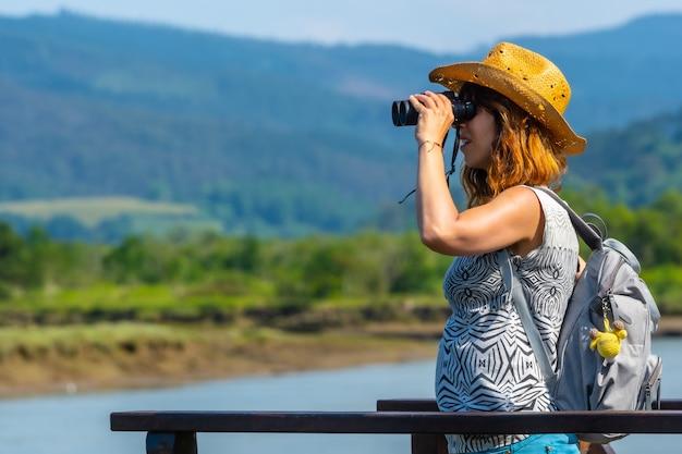 Een jonge vrouw kijkt naar de vogels vanaf de houten pieren van de urdaibai-moerassen, een biosfeerreservaat in bizkaia naast mundaka. baskenland