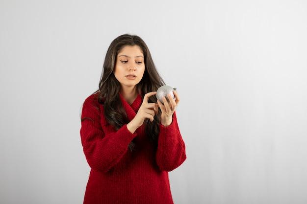 Een jonge vrouw kijkt naar een kerstbal.