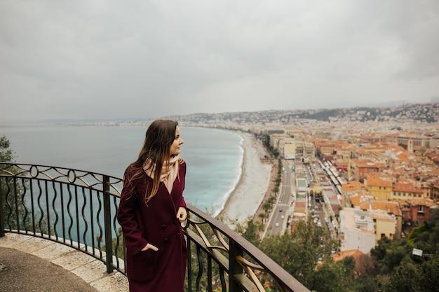 Een jonge vrouw kijkt naar nice stadsgezicht vanaf een uitkijkpunt op een heuvel.