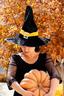 Een jonge vrouw kleedde zich als een heks met een grote pompoen