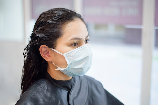 Een jonge vrouw krijgt een knipbeurt in een kapsalon, die gezichtsmasker draagt