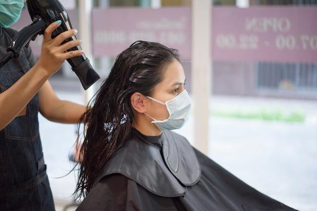 Een jonge vrouw krijgt een knipbeurt in een kapsalon en draagt een gezichtsmasker ter bescherming covid-19