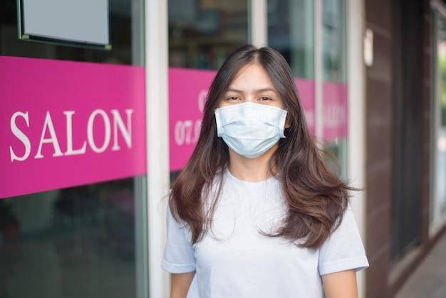 Een jonge vrouw krijgt een knipbeurt in een kapsalon, het dragen van gezichtsmasker voor bescherming covid-19, veiligheidsconcept salon