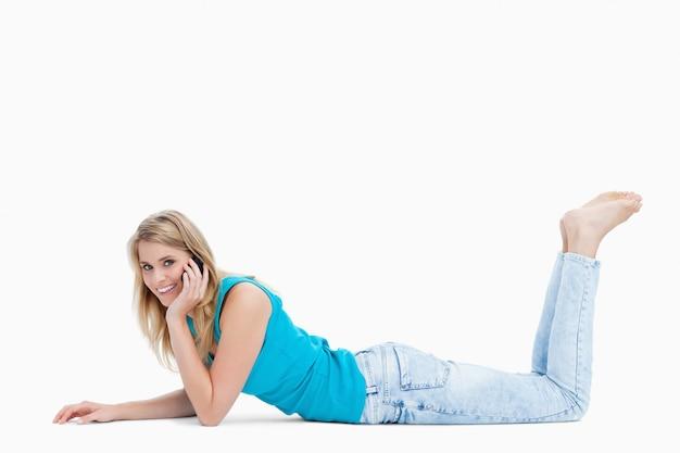 Een jonge vrouw lacht naar de camera en praat met haar mobiele telefoon