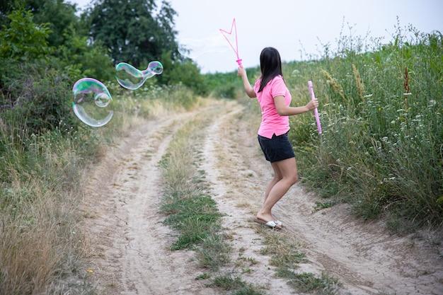 Een jonge vrouw lanceert enorme zeepbellen op de achtergrond prachtige natuur, achteraanzicht.