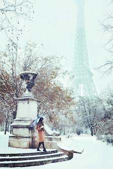 Een jonge vrouw loopt in een besneeuwde winter parijs tegen de eiffeltoren