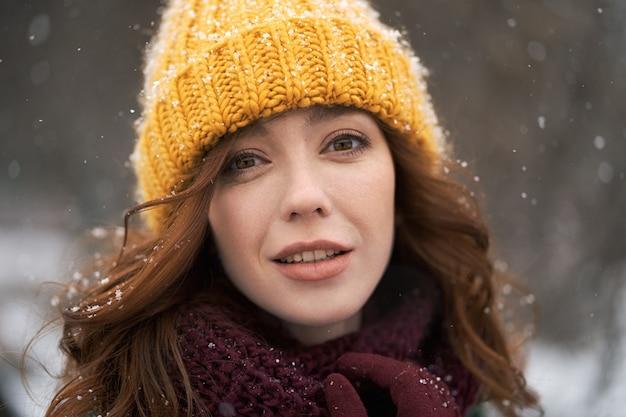 Een jonge vrouw loopt in een zonnige besneeuwde stad. ze draagt een nepbontjas, een gele gebreide muts en een sjaal. ze is erg gelukkig.