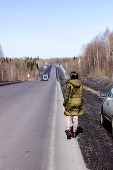 Een jonge vrouw loopt langs de kant van de weg. weg in het bos.