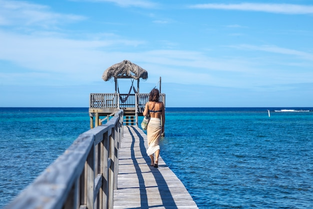 Een jonge vrouw loopt langs een houten wandelpad boven de caribische zee op roatan island. honduras